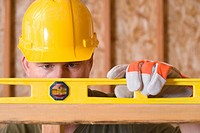 Builder in hardhat using spirit level, close-up