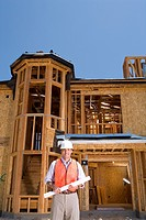 Builder in hardhat on site, smiling, portrait, low angle view