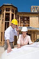 Man and woman in hardhats looking at blueprint by partially built house, man on mobile phone (thumbnail)