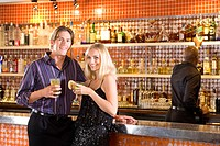 Young couple at bar with drinks, smiling, portrait