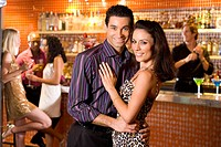 Young couple arm in arm in bar, smiling, portrait