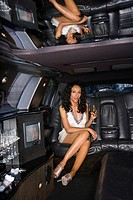 Young woman with drink in limousine, portrait