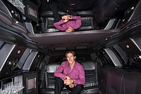 Young man with drink in limousine, reflection in ceiling, smiling, portrait