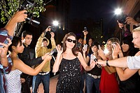 Paparazzi taking photographs of young woman in sunglasses, low angle view (thumbnail)