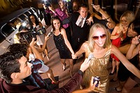 Small group of young women and bodyguard surrounded by paparazzi, elevated view (thumbnail)