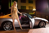Young woman by open door of car, low angle view, night