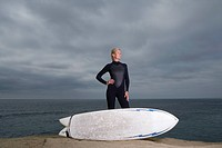 Female surfer in wetsuit with surfboard by beach, hand on hip
