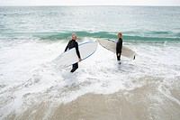 Male and female surfers in water on beach, elevated view