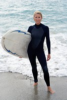 Female surfer in wetsuit on beach, portrait