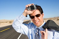 Businessman in sunglasses with mobile phone on side of road, hand to head, smiling, close-up