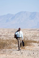 Businessman with briefcase in desert, jacket over shoulder