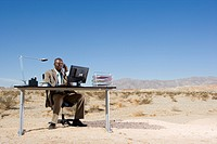 Businessman at desk in desert, using telephone and computer, low angle view