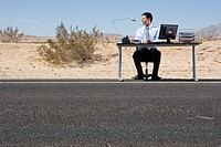 Businessman at desk on side of road in desert, low angle view