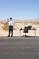 Businessman by desk on side of road in desert, using telephone, looking into distance, low angle view