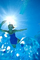 Woman in swimming pool, portrait, underwater view lens flare