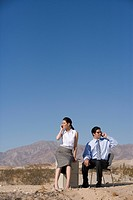 Businessman and woman in desert using mobile phones, low angle view