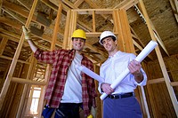 Young male architect with blueprint by builder in partially built house, smiling, portrait, low angle view