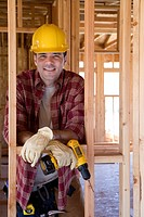 Builder in hardhat with drill in partially built house, portrait