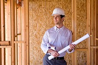 Architect with blueprints in hardhat in partially built house