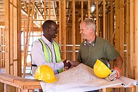 Businessman and builder shaking hands by blueprints in partially built house, smiling