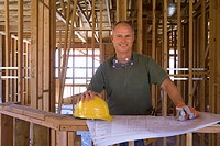 Builder with blueprints in partially built house, smiling, portrait