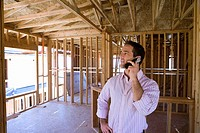 Businessman using mobile phone in partially built house