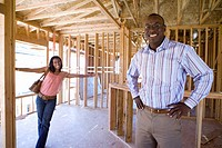 Woman smiling at businessman with hands on hips in paritally built house, portrait (thumbnail)