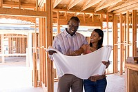 Young couple looking at blueprints in partially built house, smiling