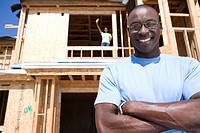 Man with arms crossed outside partially built house, smiling, portrait, low angle view