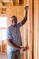 Man measuring wall in partially built house, smiling, portrait