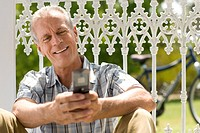 Mature man using mobile phone outdoors, sitting against fence, smiling