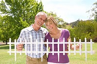 Mature couple holding small picket fence outdoors, smiling, portrait