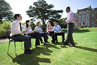 Businessmen and women with folders in training course by manor house (thumbnail)