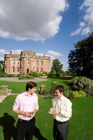 Man in conversation with friend in grounds by manor house, elevated view (thumbnail)