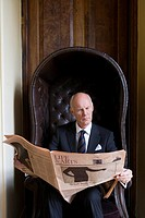 Senior man reading newspaper in armchair