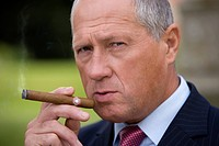 Mature businessman smoking cigar, portrait, close-up