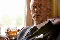 Senior businessman with drink, portrait, close-up