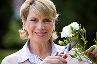 Mature woman pruning bush with secateurs, smiling, portrait (thumbnail)