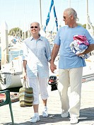 Senior couple walking hand in hand on jetty, smiling
