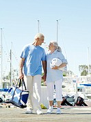 Senior couple holding hands on jetty, smiling at each other, low angle view