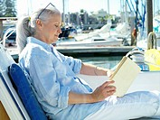 Mature woman on boat reading book, side view