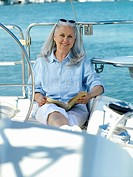 Mature woman on boat with book, smiling, portrait