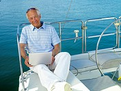 Senior man on boat with laptop computer, smiling, portrait