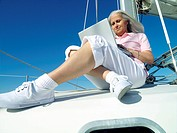 Mature woman using laptop computer on boat, low angle view