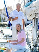 Mature couple on deck of boat with drinks, smiling, portrait