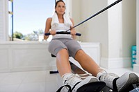 Young woman on rowing machine, low angle view (thumbnail)