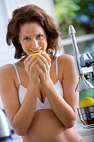 Young woman in underwear with orange by juicer, smiling, portrait