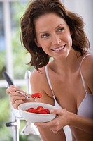 Young woman in underwear eating strawberries and cereal, smiling