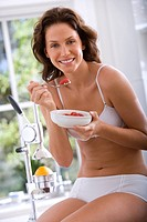 Young woman in underwear eating breakfast, smiling, portrait