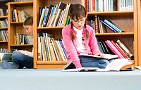 Girl 9-11 and friend reading in library